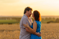 Adult farmer and wife spend time in the field. A moment before the kiss. - PhotoDune Item for Sale