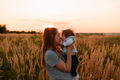 A mother walks in the field with her little daughter in her arms. - PhotoDune Item for Sale