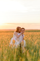 Bride and groom in a wheat field. A man carries a beloved on his back. - PhotoDune Item for Sale