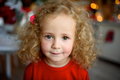 Portrait of a little beautiful girl with curly hair. The girl is dressed in a Christmas sweatshirt. - PhotoDune Item for Sale