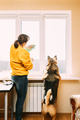 Woman Of Fifty In Yellow Sweater Washes Dusty Window In Apartment. 50 Year Old Woman Cleans Windows - PhotoDune Item for Sale