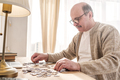 Senior caucasian man working on a puzzle - PhotoDune Item for Sale