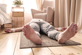Caucasian man meditating on a wooden floor and lying in Shavasana pose - PhotoDune Item for Sale