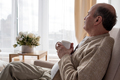 Portrait of relaxed senior man sitting on sofa with warm drink - PhotoDune Item for Sale