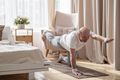 Senior caucasian men practices yoga asana chakravakasana, bird pose at home - PhotoDune Item for Sale
