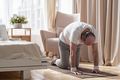 Senior man working out at home in living room, doing yoga exercise on mat. - PhotoDune Item for Sale