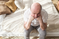 Sad caucasian man sitting on his bed with his head on his hand - PhotoDune Item for Sale
