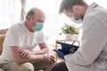 Doctor writing medical prescription to elderly man - PhotoDune Item for Sale