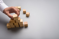 Businessman arranging wooden cubes in pyramid shape - PhotoDune Item for Sale