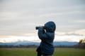 Toddler boy standing outside looking through binoculars - PhotoDune Item for Sale