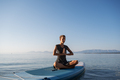 Young woman meditating on sup board floating on sea water - PhotoDune Item for Sale