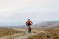 lone male cyclist riding on mountain road - PhotoDune Item for Sale