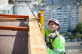 Industrial climber measuring with level tube during construction works - PhotoDune Item for Sale