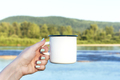 Woman holding enamel mug with river view - PhotoDune Item for Sale