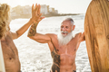 Multi generational surfer friends hands five on the beach after surf session - PhotoDune Item for Sale