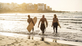 Multi generational surfer friends having fun while surfing on beach - Main focus on senior man - PhotoDune Item for Sale