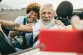 Trendy senior couple having fun in convertible car - PhotoDune Item for Sale