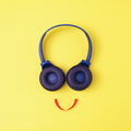 Headphones on a yellow background in the form of a happy face with a smile - PhotoDune Item for Sale