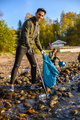 Smiling man cleaning the ocean with volunteers on sunny day - PhotoDune Item for Sale