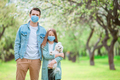 Family of father and daughter in blooming cherry garden in masks - PhotoDune Item for Sale
