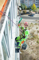 Industrial climber on building during winterization works, looking up at camera and smiling - PhotoDune Item for Sale
