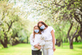 Family of mother and daughter in blooming cherry garden in masks - PhotoDune Item for Sale