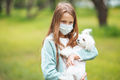 Little girl with dog wearing protective medical mask for prevent virus outdoors in the park - PhotoDune Item for Sale