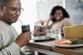Happy black father drinking yerba mate during lunch at home - PhotoDune Item for Sale