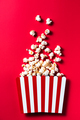Striped Popcorn Bucket Box on Red Cinemab Background. Movies and Entertainment Concept. Flat Lay . - PhotoDune Item for Sale