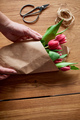 Female hands arranging pink tulips bouquet on wooden table, floristic hobby workplace - PhotoDune Item for Sale