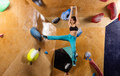 Caucasian young woman bouldering in indoor climbing gym - PhotoDune Item for Sale