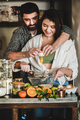 Young caucasian couple hugging baking holiday cake together at home - PhotoDune Item for Sale