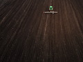 Aerial view of a modern green tractor seeding agricultural field - PhotoDune Item for Sale