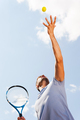 Serving a ball. Low angle view of tennis player serving a ball while standing against blue sky - PhotoDune Item for Sale