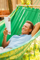 Time to relax. Happy mature man lying in hammock and reading magazine - PhotoDune Item for Sale