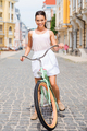 City girl. Full length of beautiful young smiling woman riding bicycle along the street - PhotoDune Item for Sale