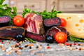 Close up of assorted dry-cured meat on the wooden background - PhotoDune Item for Sale