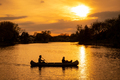 Silhouette of couple with dog kayaking in the lake at sunset - PhotoDune Item for Sale