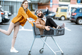 Couple riding with shopping cart on the parking outdoors - PhotoDune Item for Sale