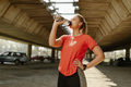 Fitness woman drinking water from bottle. Muscular young female taking a break from workout outside. - PhotoDune Item for Sale