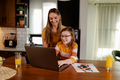 Beautiful smiling mom and cute daughter is using laptop and searching for cartoons. - PhotoDune Item for Sale