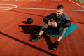 Photo of sport man using his smart phone while sitting on the floor of the sports field. - PhotoDune Item for Sale