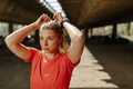 Athletic beautiful woman tying her hair. Sporty woman getting ready for workout. - PhotoDune Item for Sale