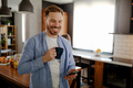Attractive Caucasian smiling man reading messages on smart phone standing at the kitchen. - PhotoDune Item for Sale