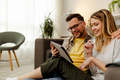 Smiling young couple sitting on the floor of their apartment and shopping through Internet. - PhotoDune Item for Sale