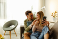 Loving couple sitting on the sofa at home and taking a selfie. - PhotoDune Item for Sale