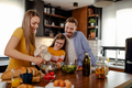 Happy young family preparing healthy food together in kitchen. - PhotoDune Item for Sale