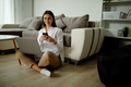 Woman studying at home reading an sms on her phone with a smile as she sits on the floor. - PhotoDune Item for Sale