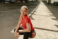 Young woman runner resting after running workout. Female fitness model posing under a bridge. - PhotoDune Item for Sale