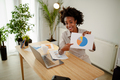 Afro American businesswoman showing business diagram at paper while looking at camera and smiling. - PhotoDune Item for Sale